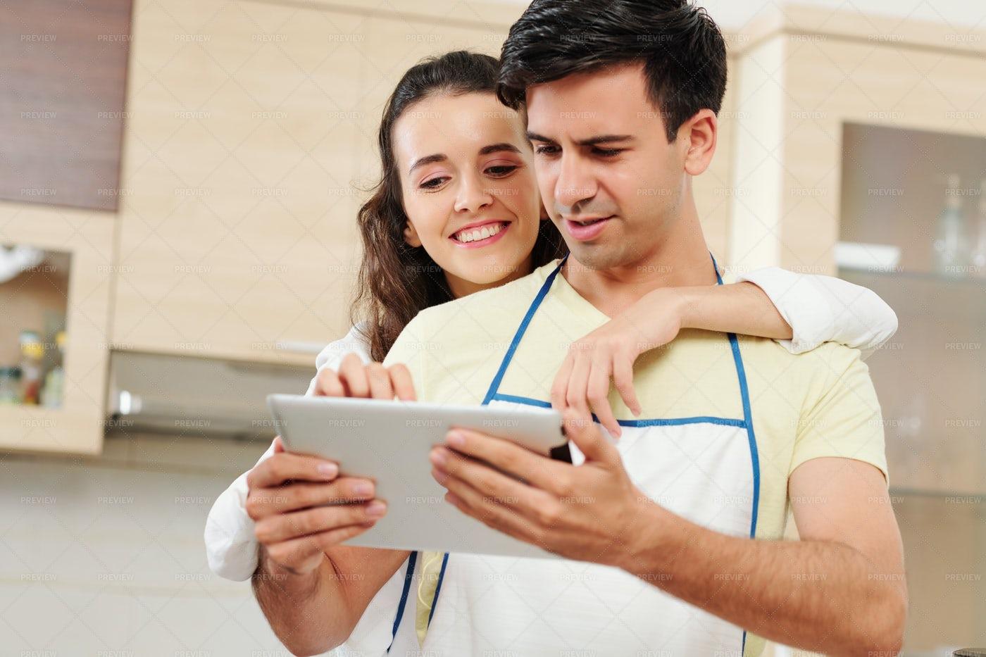 Couple Reading Recipe On Tablet: Stock Photos