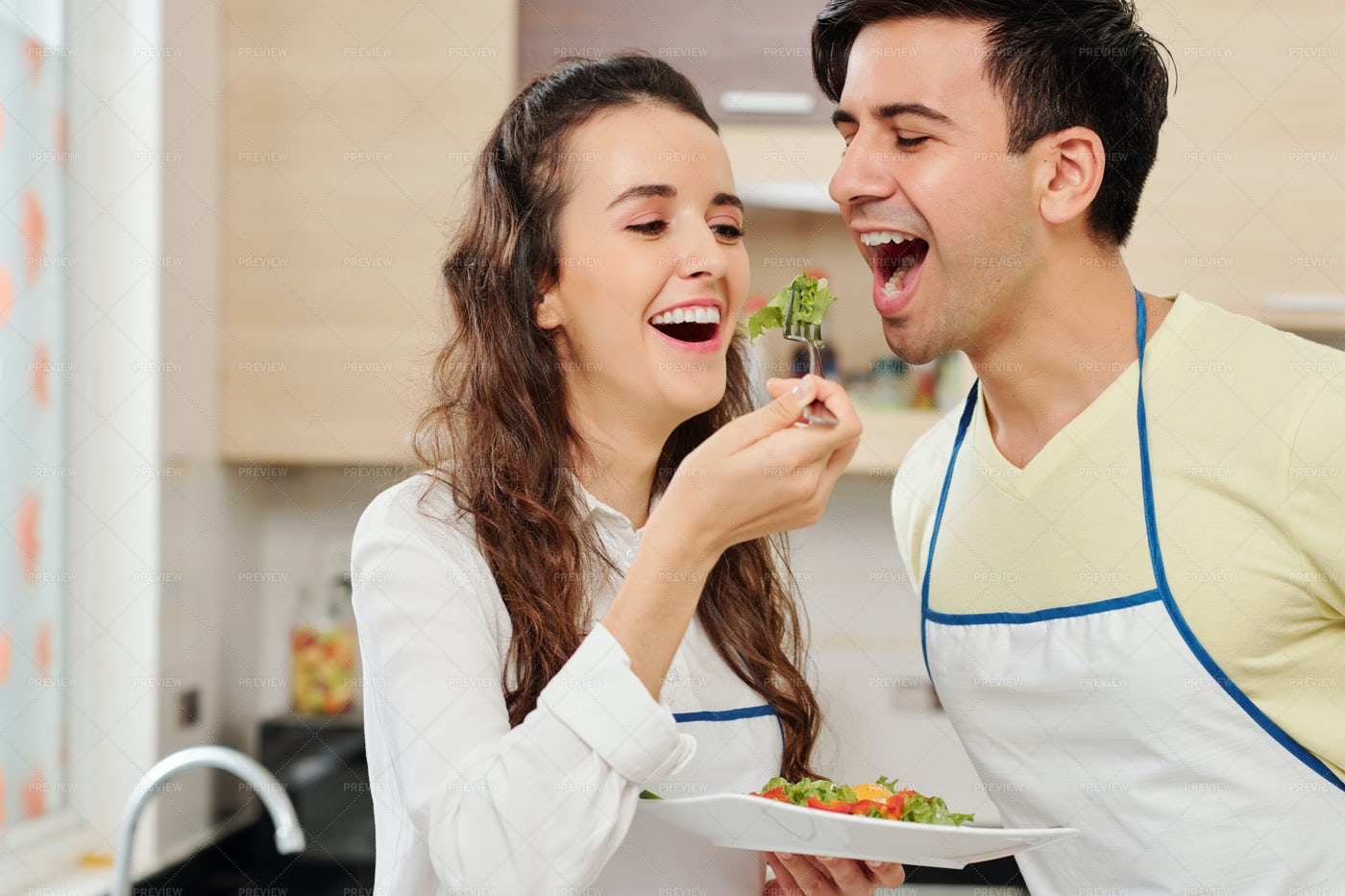 Cheerful Woman Feeding Husband: Stock Photos