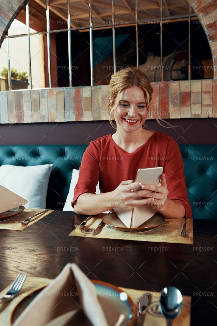 Woman Sitting In Restaurant And Texting: Stock Photos