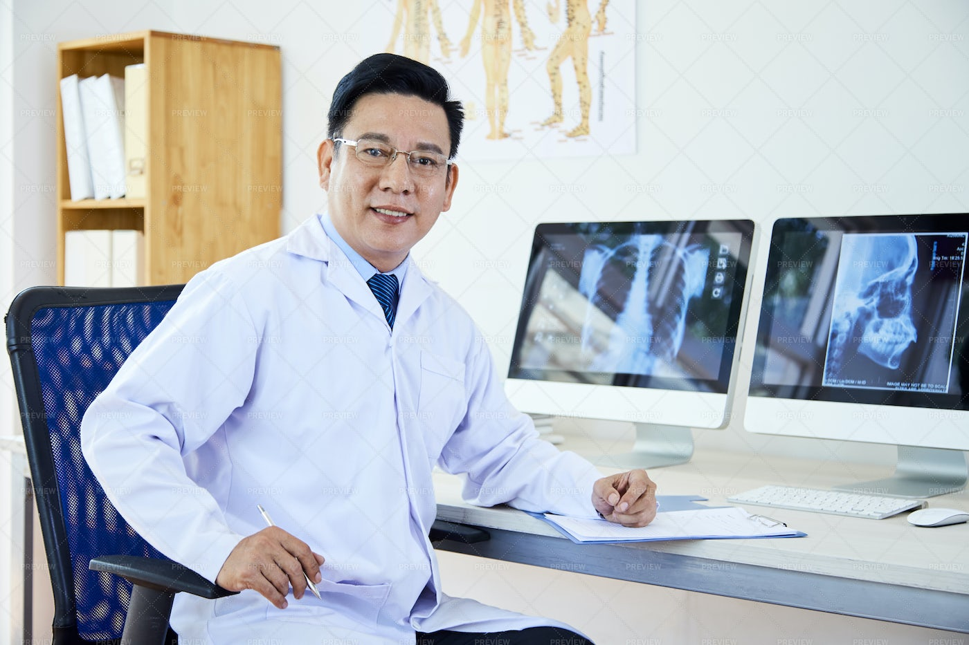 Asian Doctor Working At Office: Stock Photos