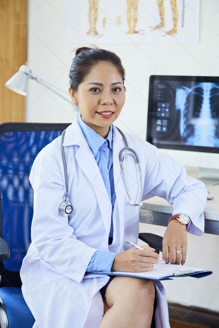 Asian Female Doctor Working At Office: Stock Photos