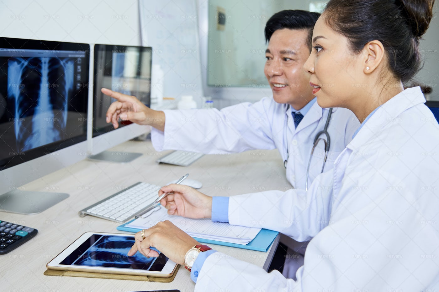 Couple Of Doctors Discussing X-ray: Stock Photos