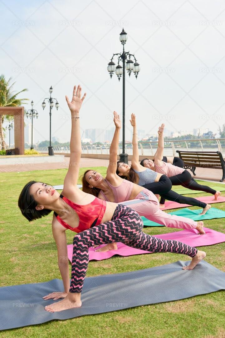 Women In Row Doing Yoga Asana Outdoors: Stock Photos