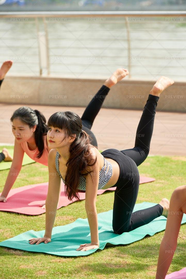 Sportswomen Doing Yoga Exercise In Team: Stock Photos