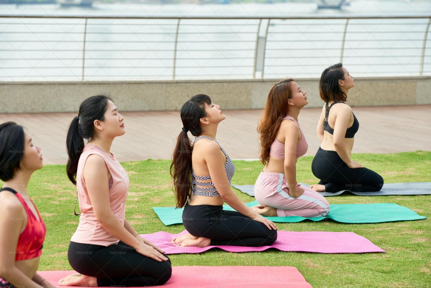 Meditating Ethnic Women In Row Outdoors: Stock Photos