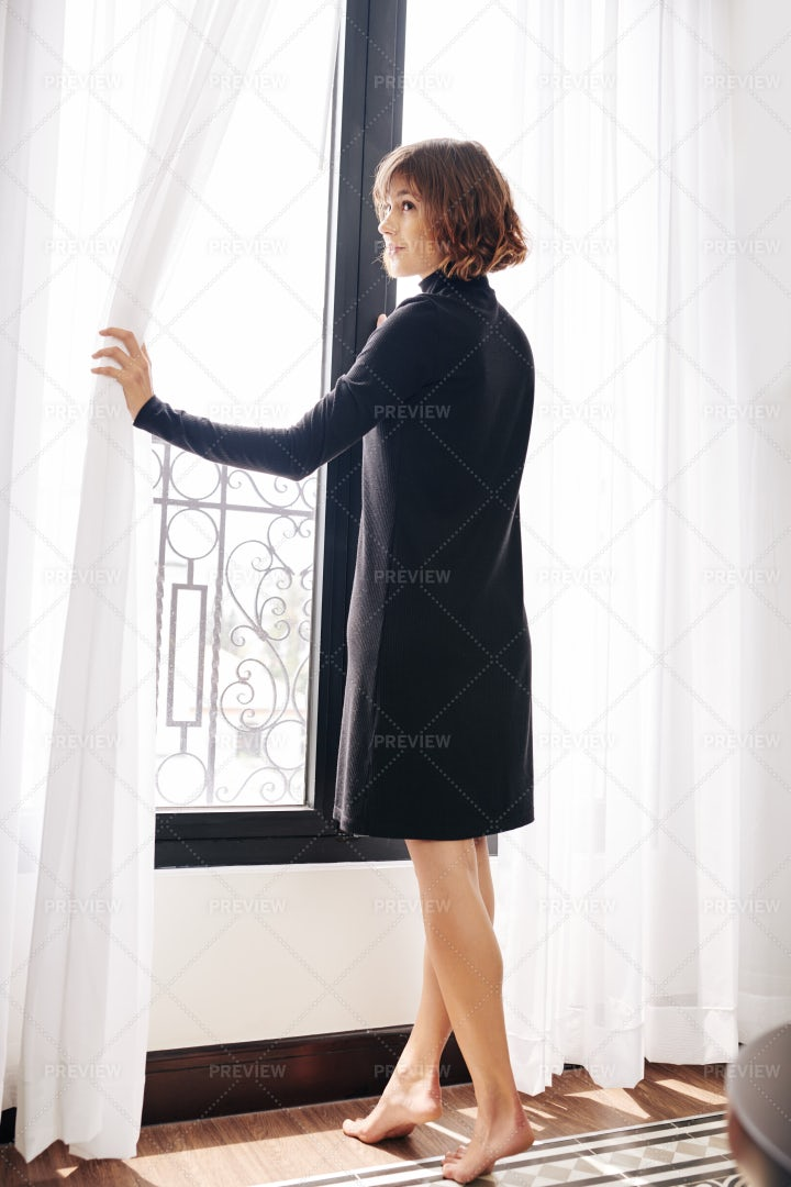 Young Barefoot Woman Opening Curtains: Stock Photos