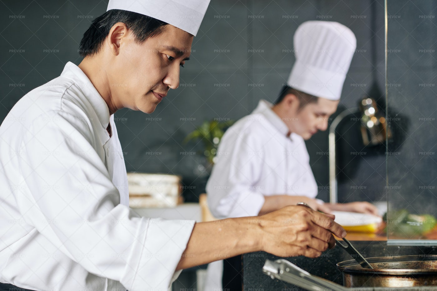 Asian Man Cooking In The Kitchen: Stock Photos