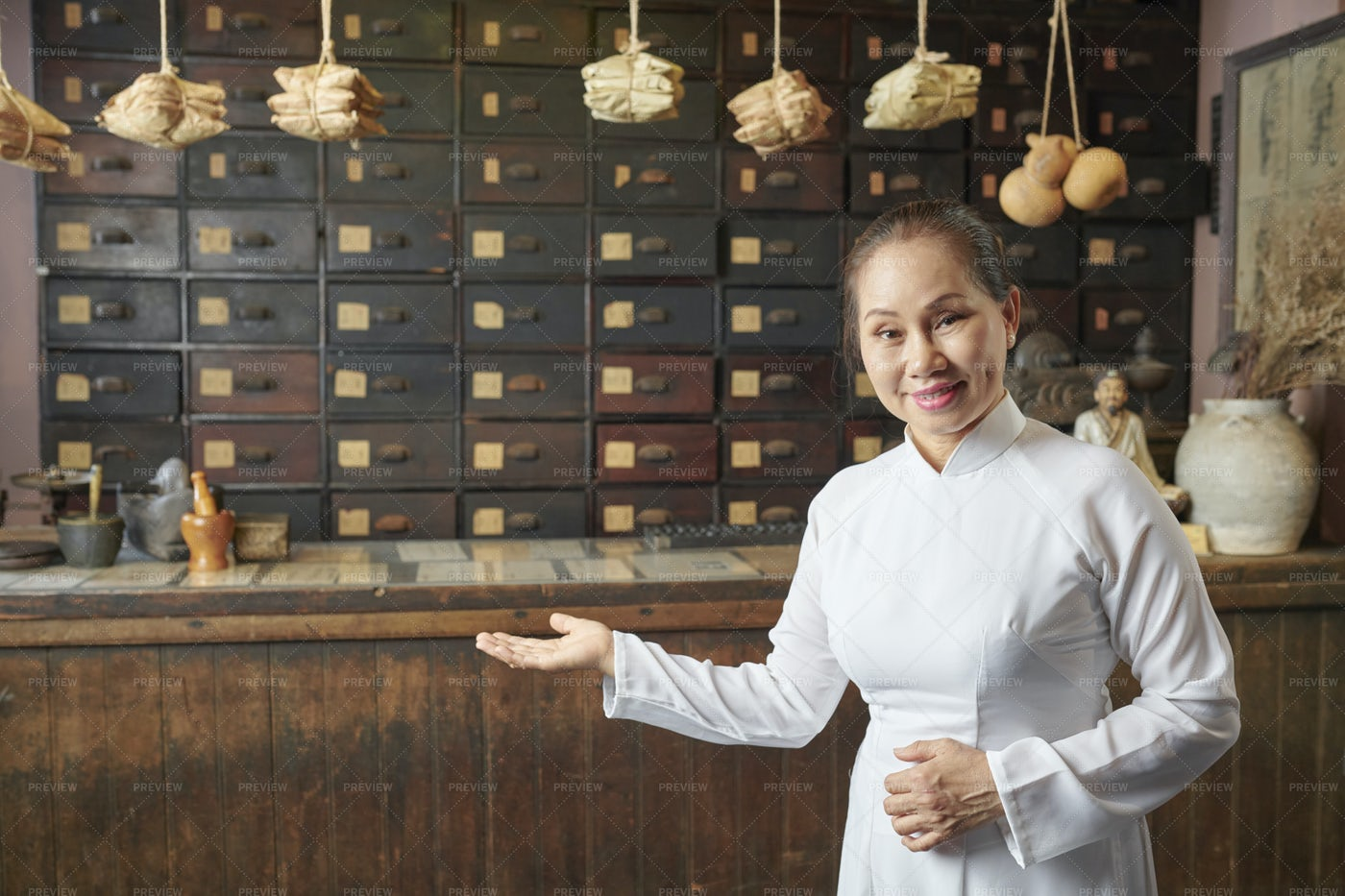 Woman Inviting To Herbs Store: Stock Photos