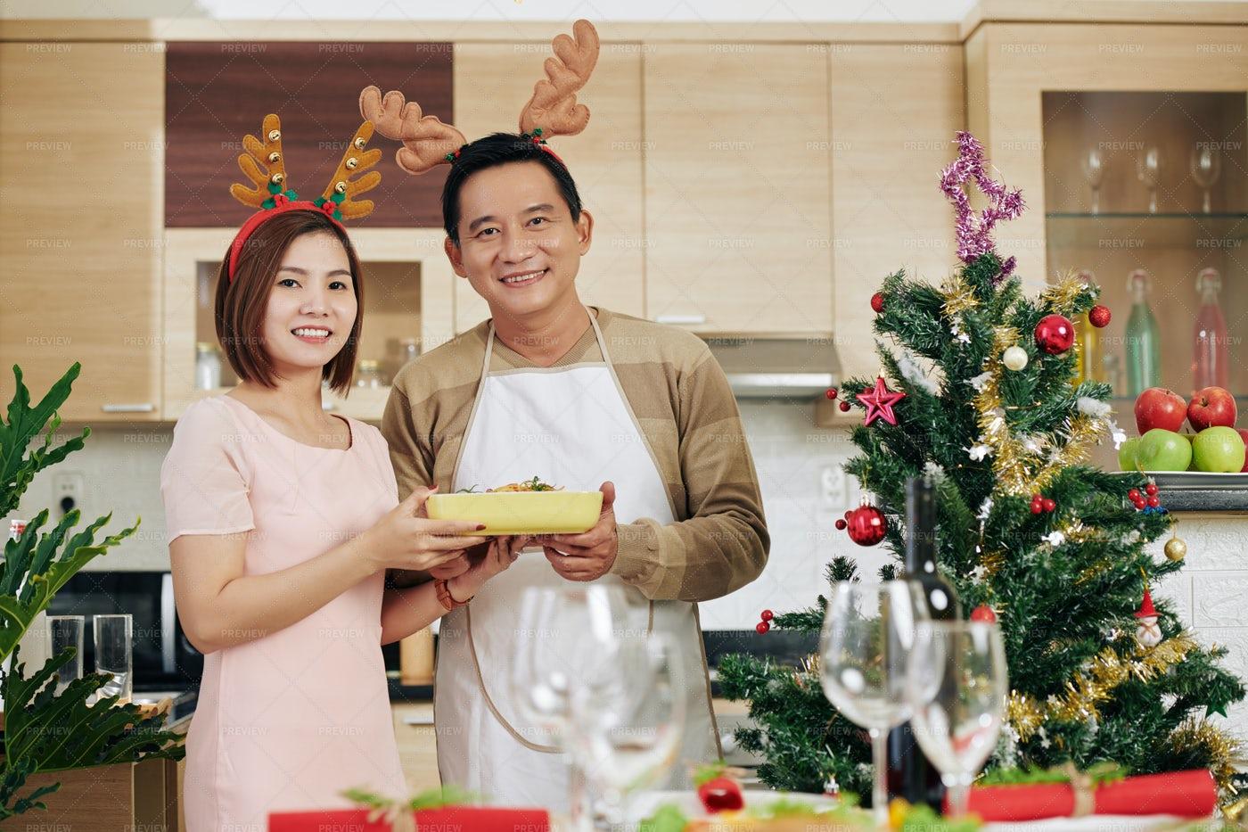 Couple Serving Christmas Dinner: Stock Photos
