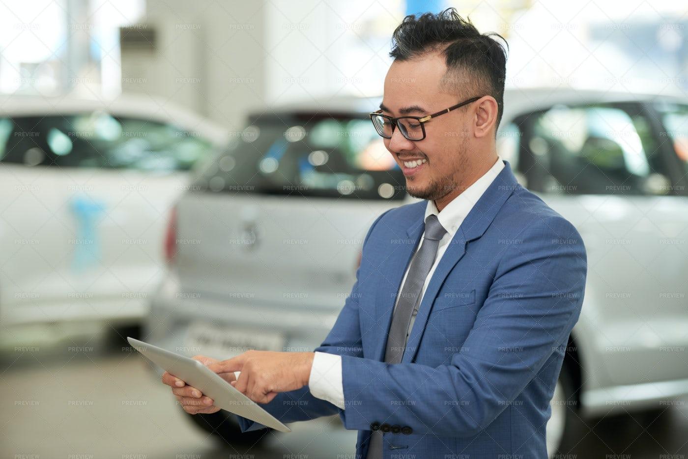 Salesman Using Tablet Pc In Car Salon: Stock Photos