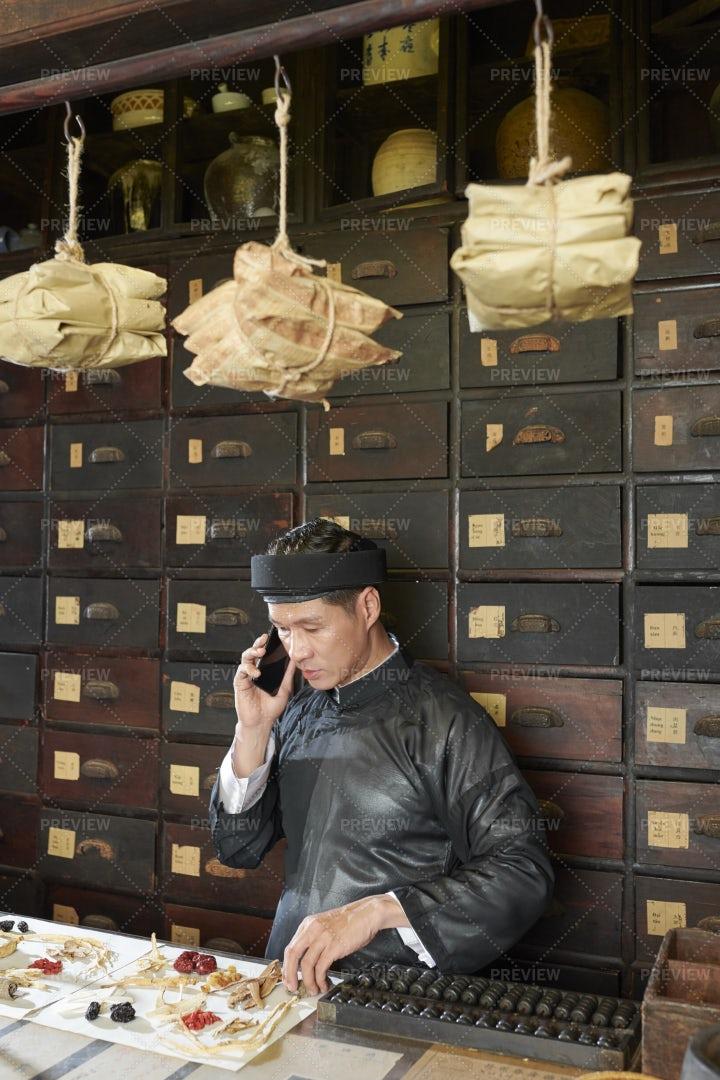 Mature Asian Man Packing Order In: Stock Photos