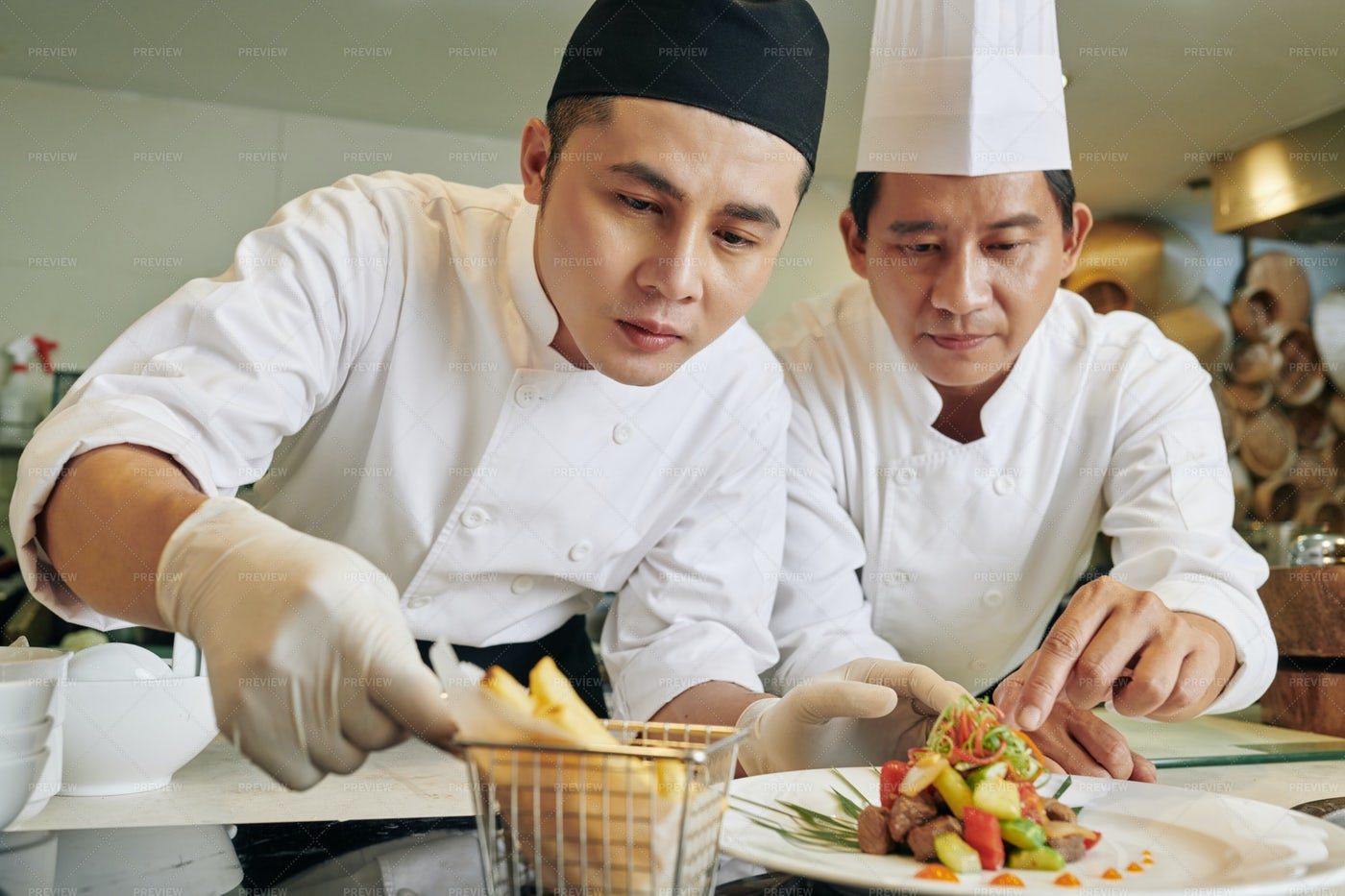 Two Chefs Decorating The Salad: Stock Photos
