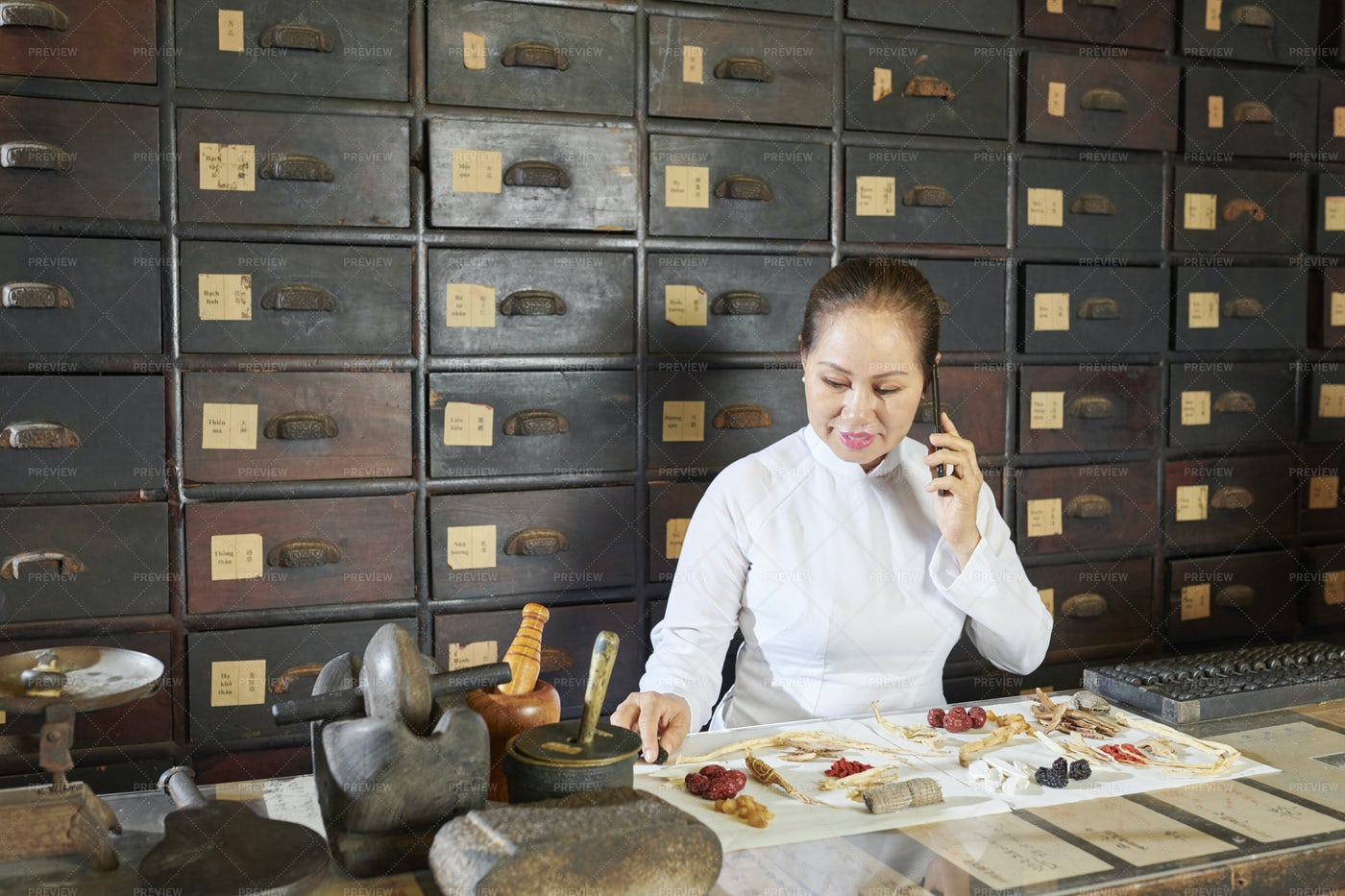 Mature Asian Woman Packing Orders In: Stock Photos