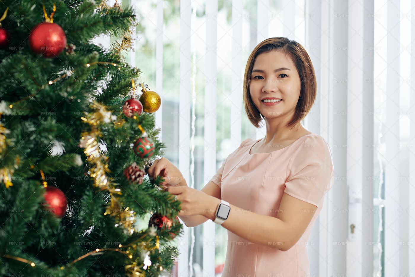Woman Hanging Baubles On Tree: Stock Photos