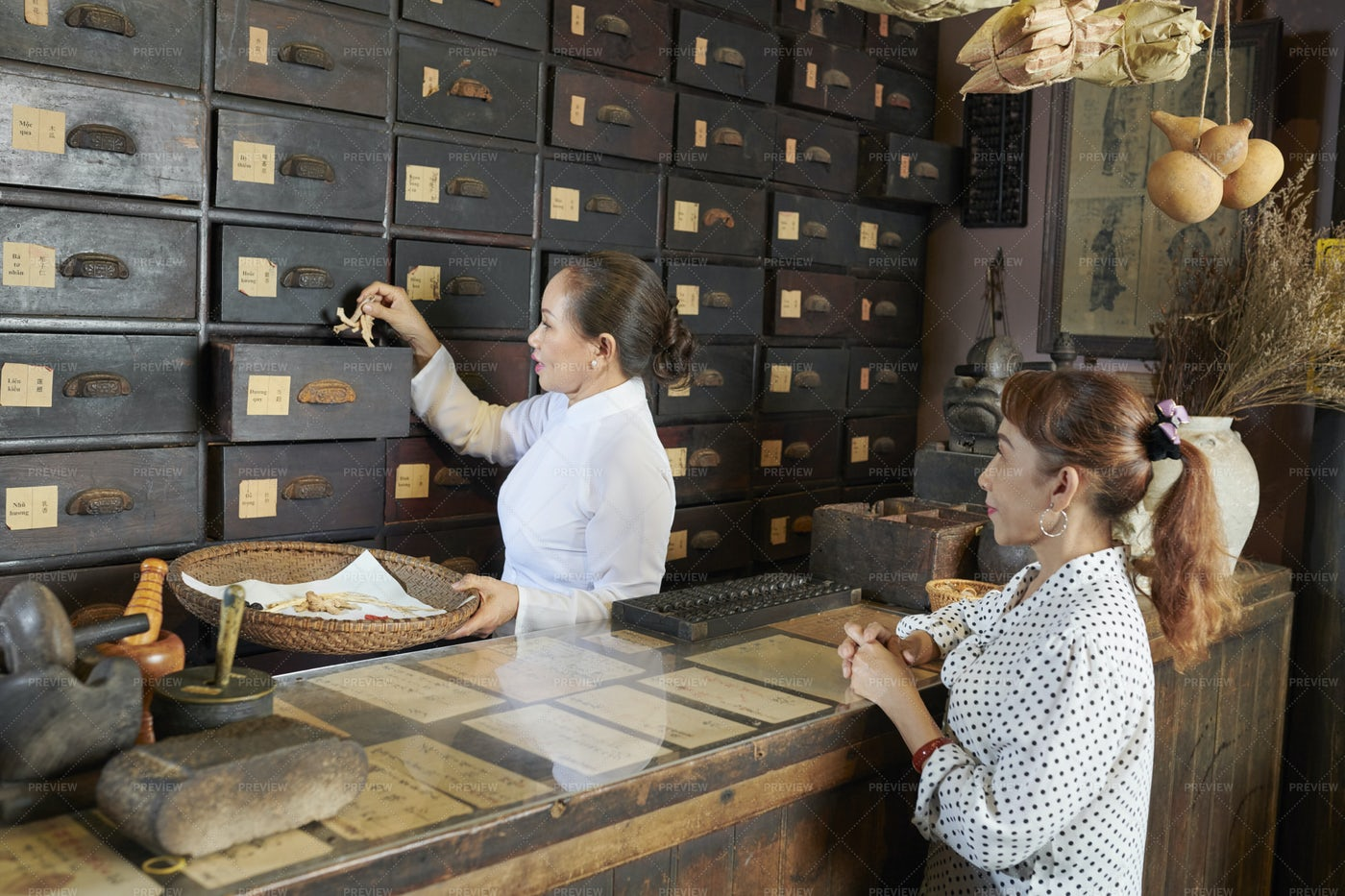 Woman Buying Dried Roots In Apothecary: Stock Photos