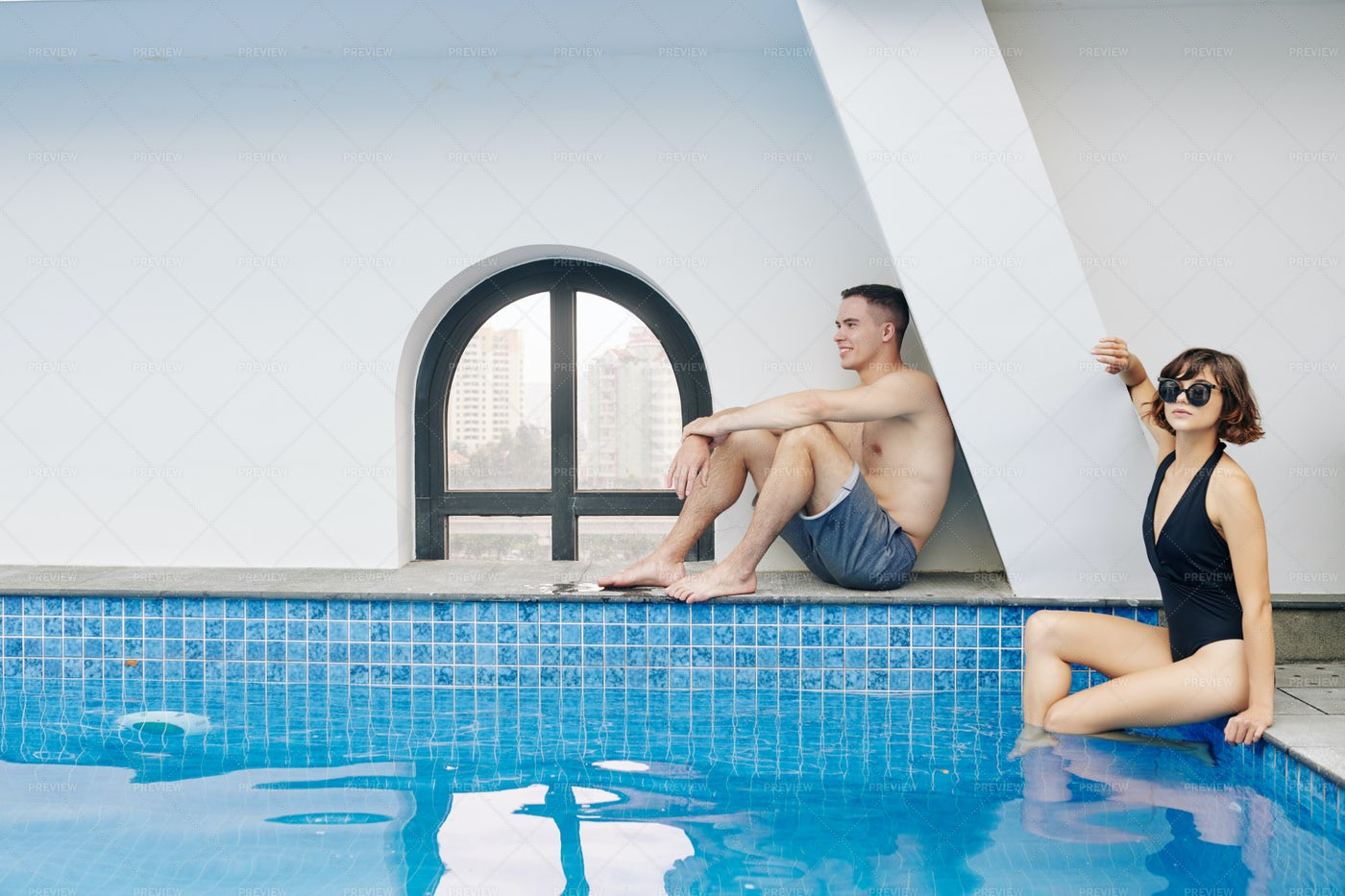 Man And Woman Sitting At Swimming Pool: Stock Photos