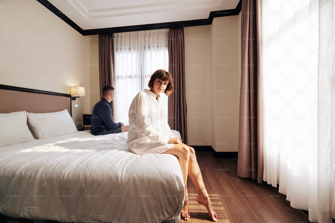 Pretty Woman Sitting On Hotel Bed: Stock Photos