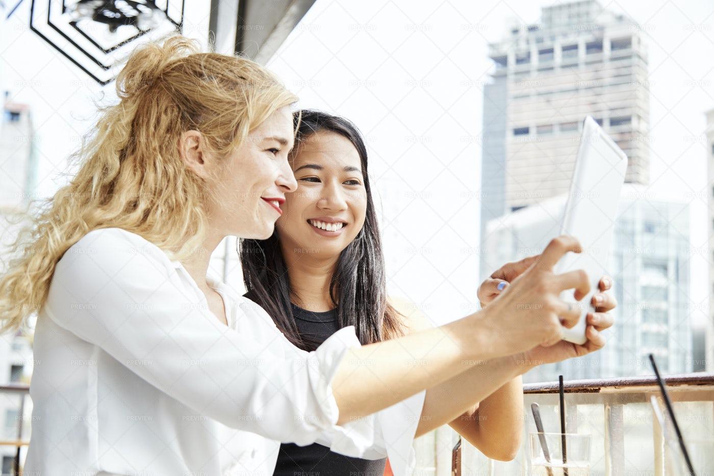 Female Friends Using App On Digital: Stock Photos