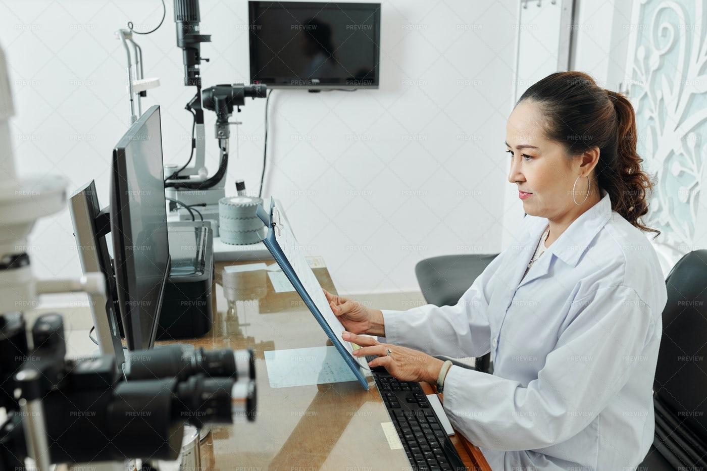 Doctor Examining Patient's Medical Card: Stock Photos