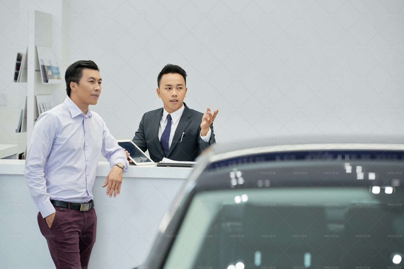 Salesman Showing Cars To Customer: Stock Photos