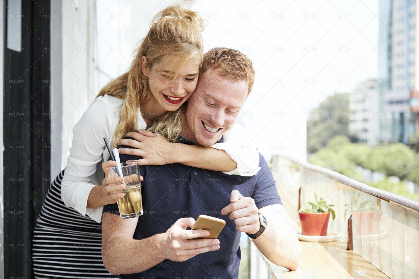 Positive Copule Checking Text Message: Stock Photos
