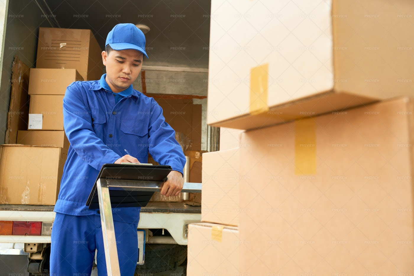 Delivery Man Checking Note: Stock Photos