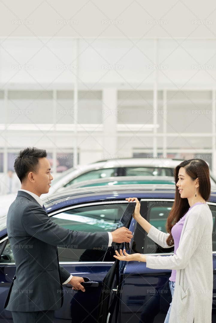 Salesman Opening Door For Customer: Stock Photos