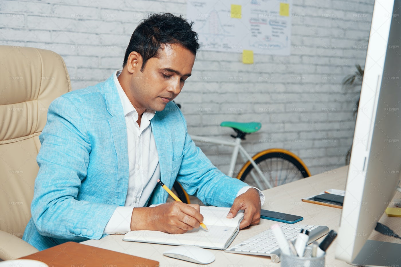 Manager Making Notes In Notepad At: Stock Photos