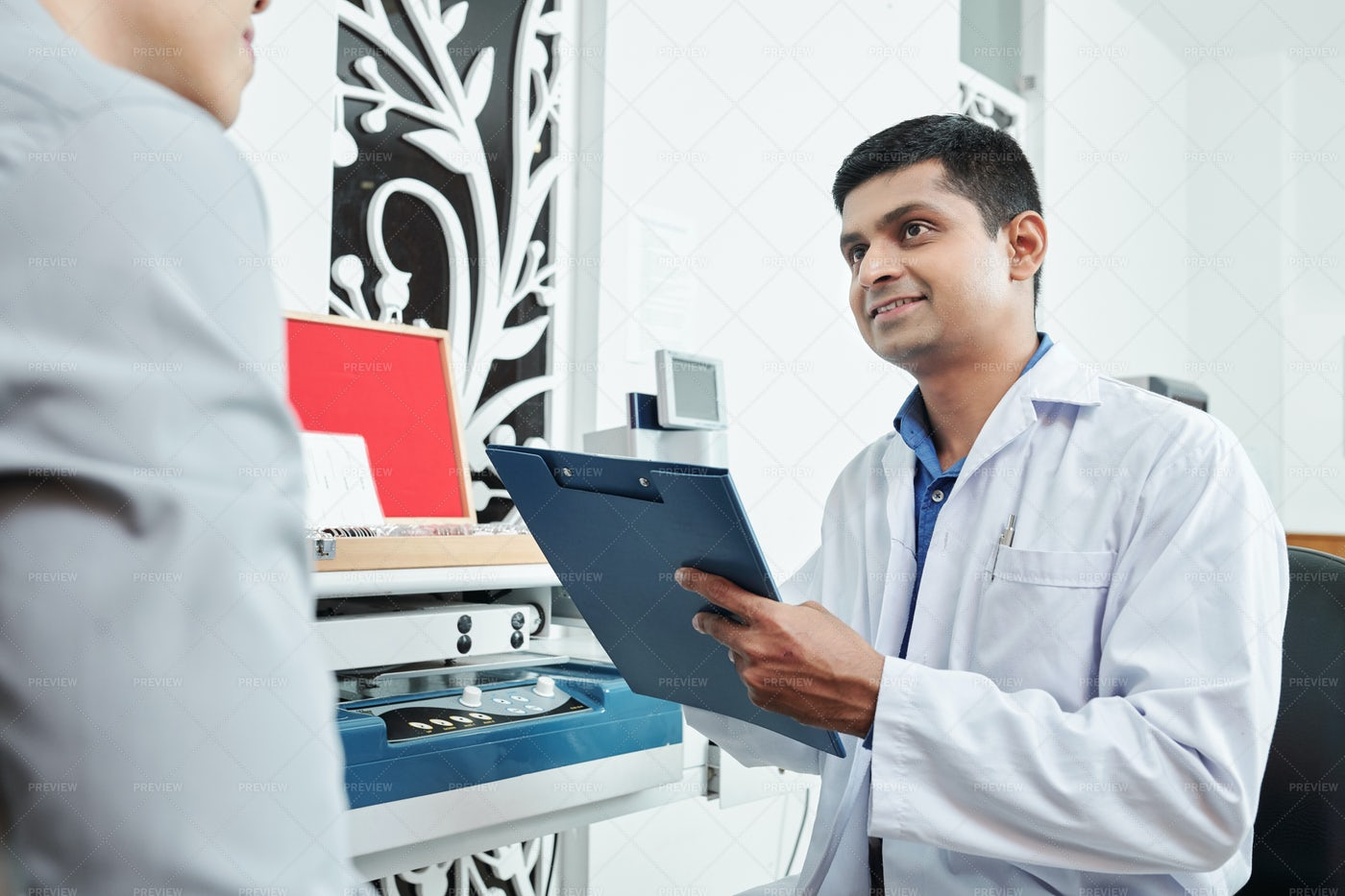 Doctor With Medical Card At Office: Stock Photos