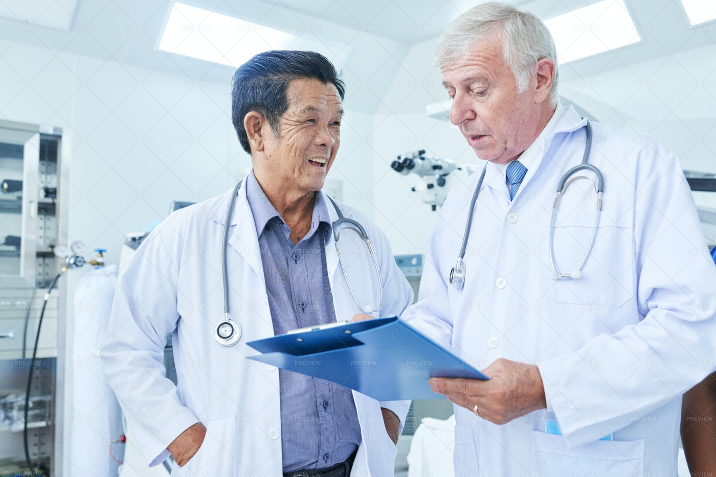 Physician Listening To Coworker: Stock Photos
