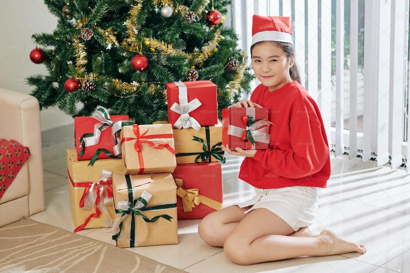 Curious Girl Opening Presents: Stock Photos