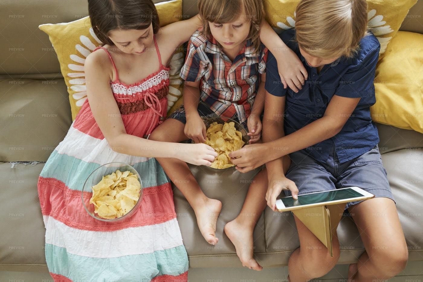Friends Enjoying Chips And Cartoon: Stock Photos