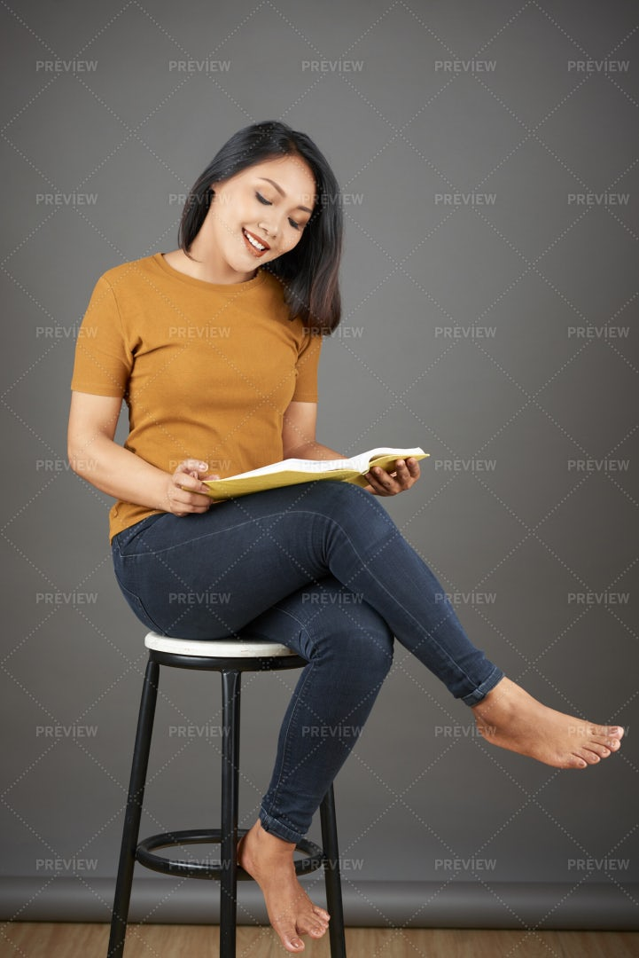 Woman Sitting On Stool With Book: Stock Photos