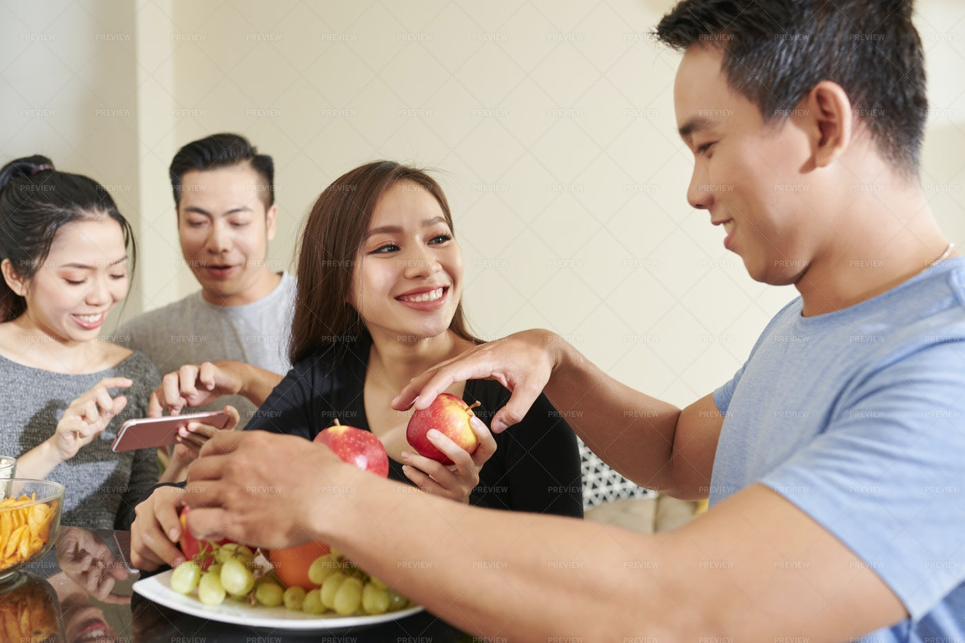Young People Eating Fruits At Party: Stock Photos