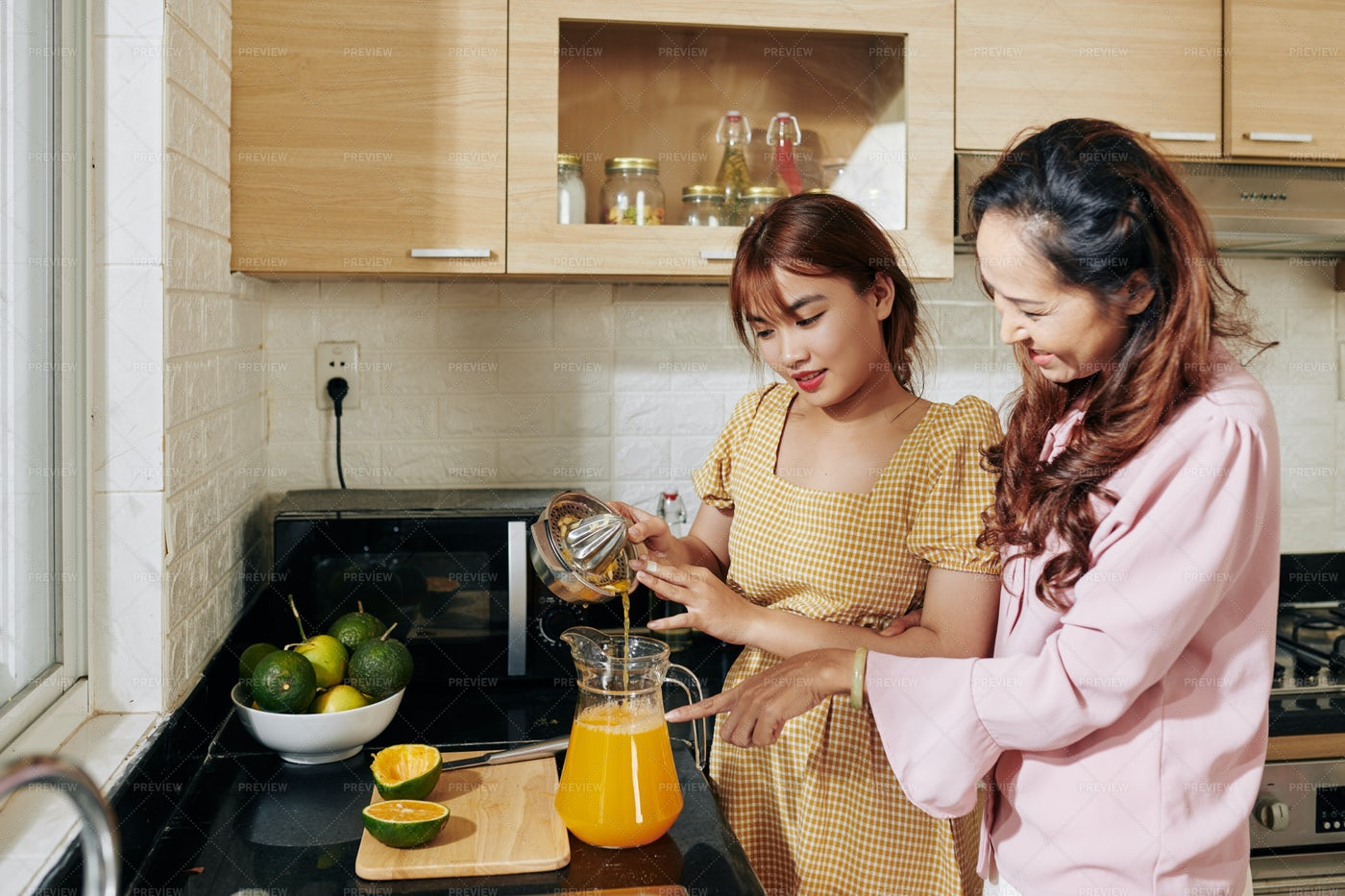 Mother And Daughter Making Juice: Stock Photos
