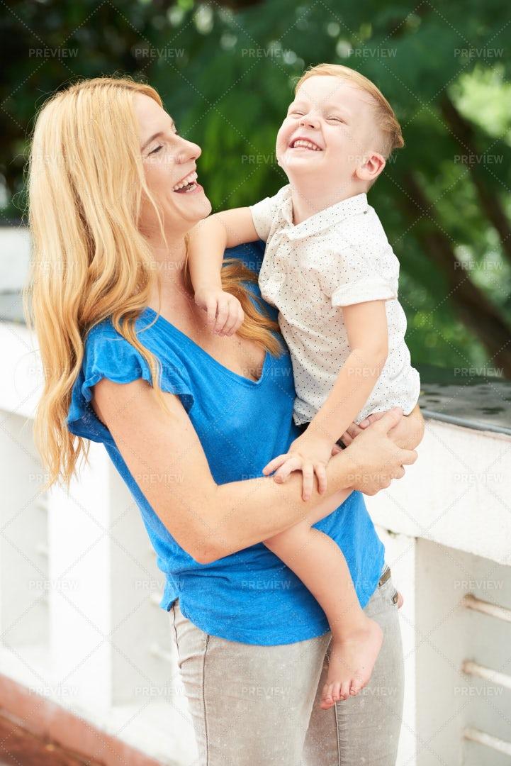 Mother Carrying Son: Stock Photos
