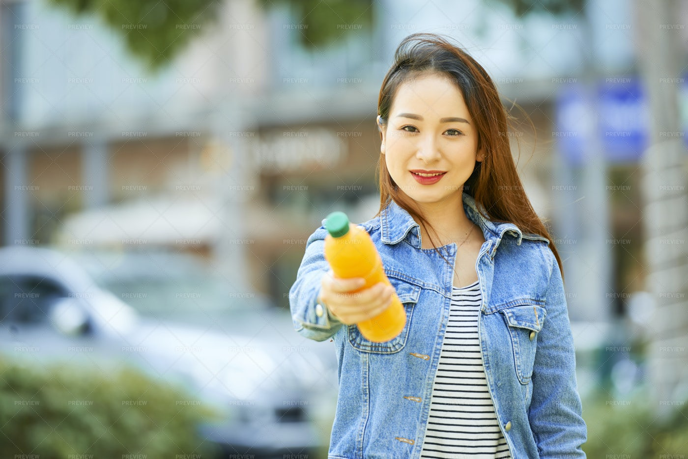 Positive Woman Giving Bottle Or Juice: Stock Photos