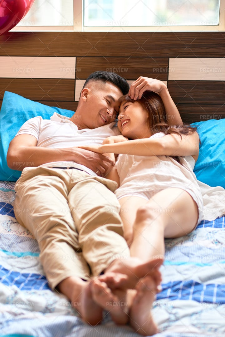 Couple Relaxing On Bed: Stock Photos