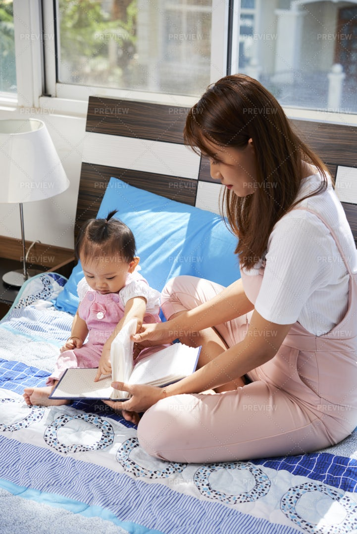 Mother Showing Book To Daughter: Stock Photos