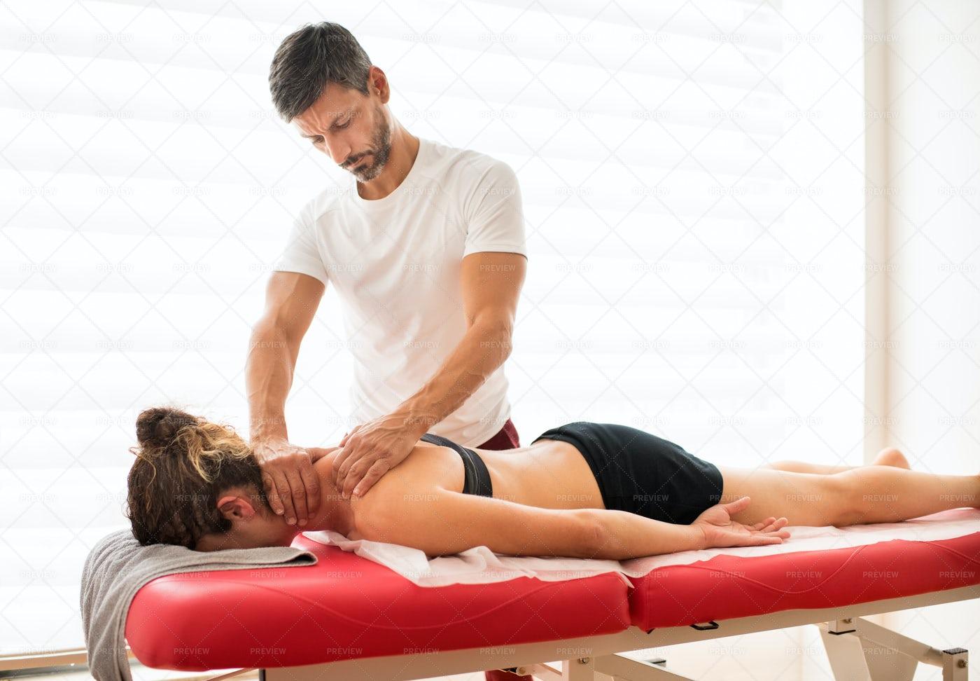 Osteopath Massaging A Female Patient: Stock Photos