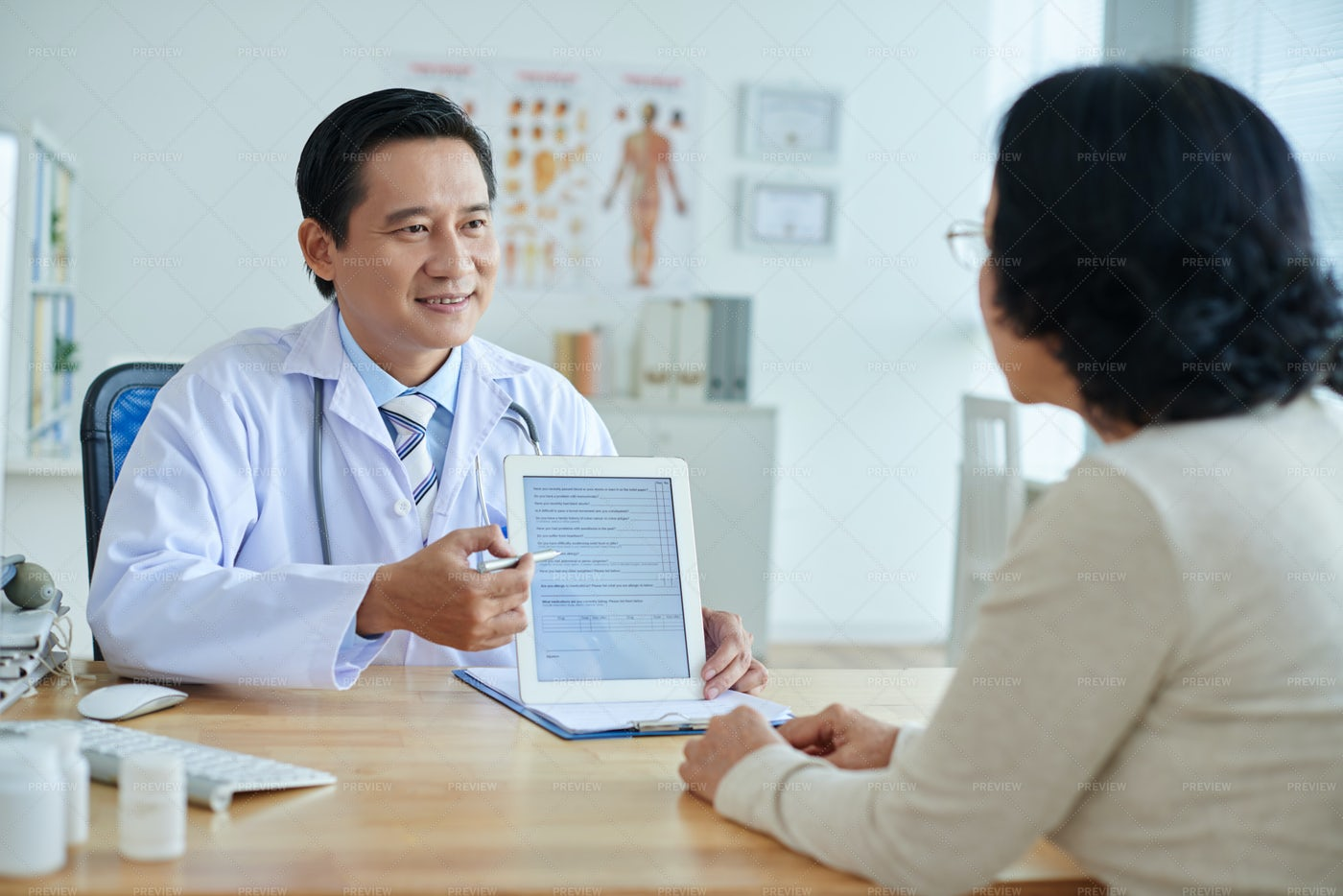 Asian Doctor Talking To Patient: Stock Photos