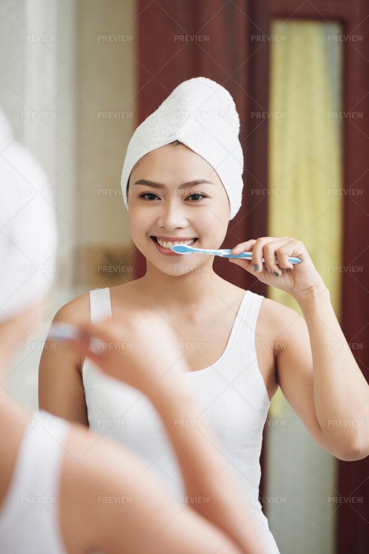 Woman Brushing Teeth In Mirror...: Stock Photos