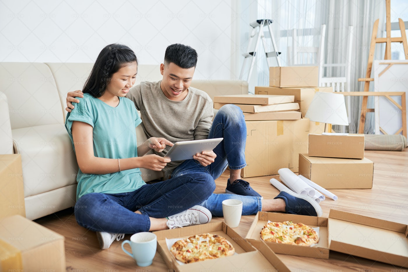 Couple With Pizza And Tablet In New...: Stock Photos
