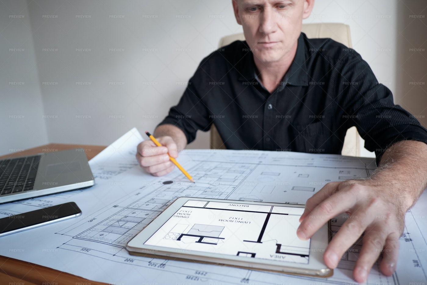 Architect Examining Blueprint: Stock Photos
