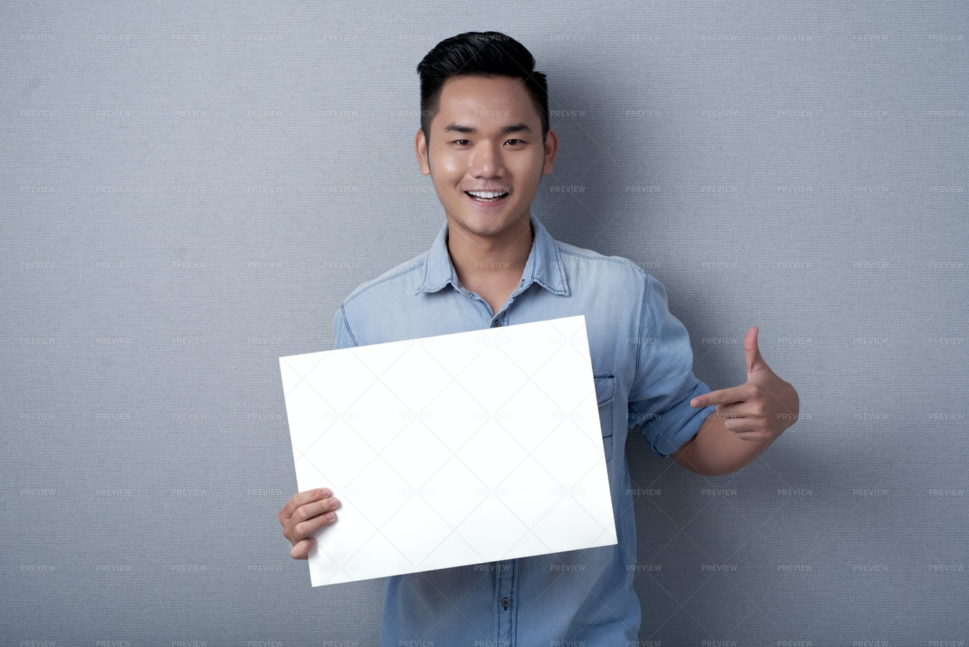 Smiling Asian Man With Sheet Of...: Stock Photos