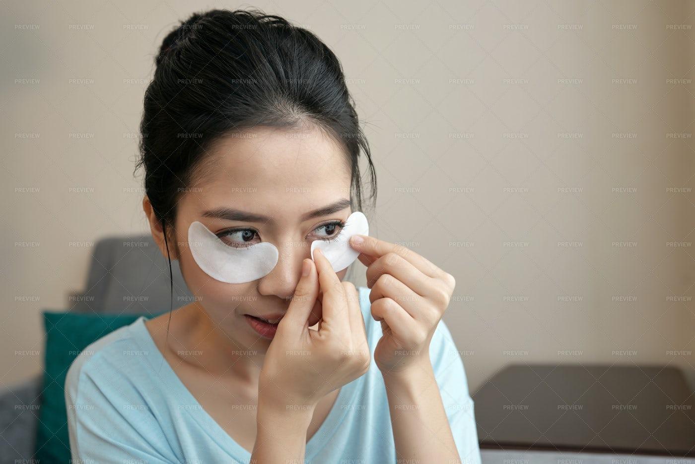Asian Woman Applying Under-eye Pads: Stock Photos