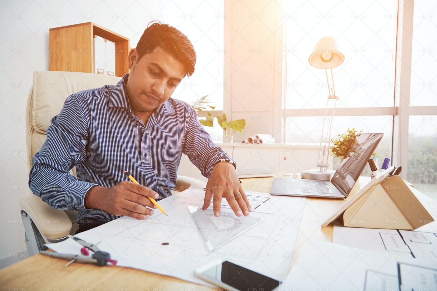 Indian Man Working On Blueprint: Stock Photos