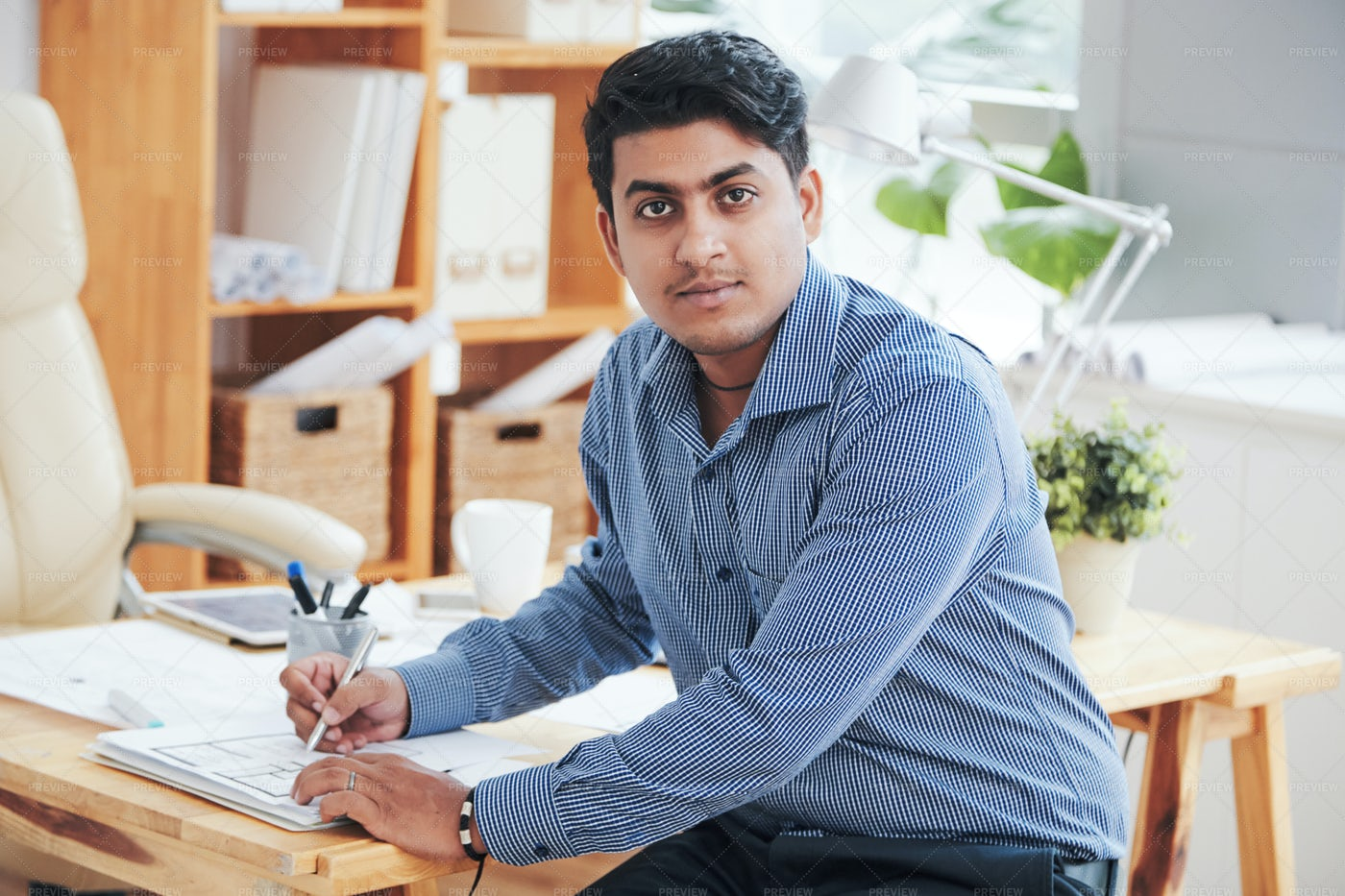 Man Working With Papers Looking At...: Stock Photos