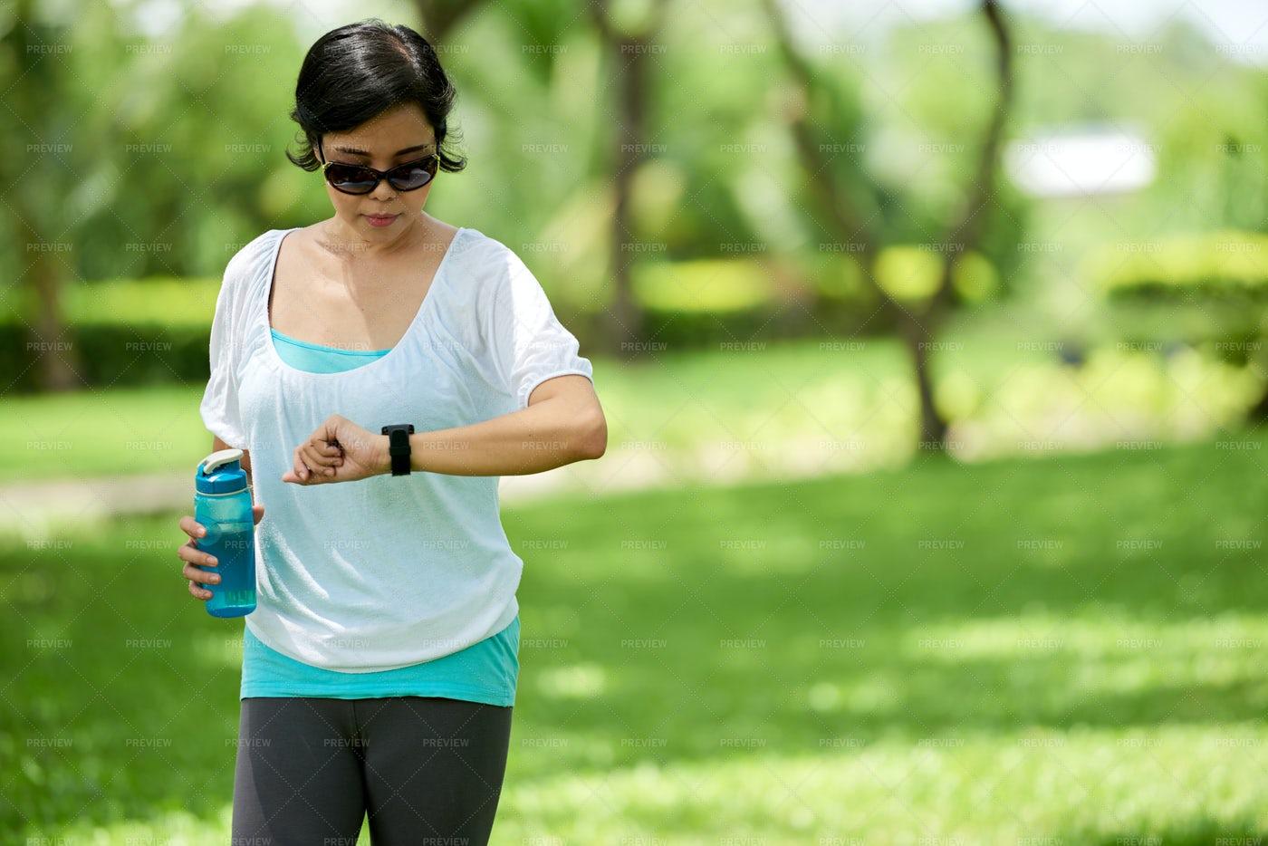 Asian Woman Checking Fitness...: Stock Photos