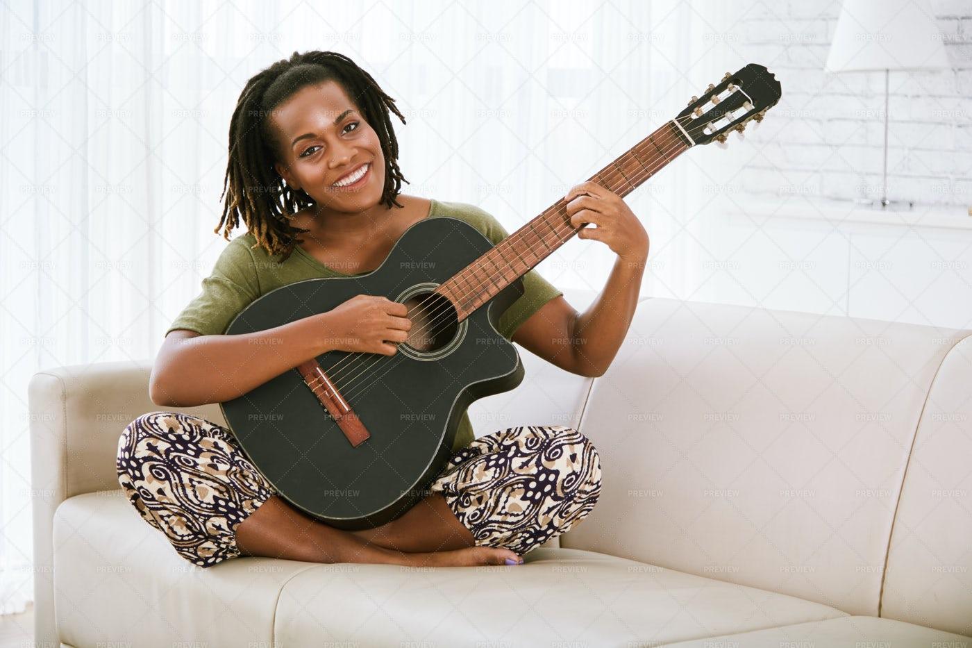 Pretty Woman Playing Guitar: Stock Photos